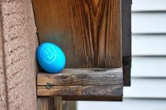关闭兴高采烈的面孔在后院装饰了在一个棚子的房檐掩藏的鸡蛋复活节彩蛋狩猎的 免版税库存照片
