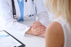 关闭再保证她的女性患者的医生手 免版税图库摄影