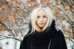 关闭冬天画象:在一件温暖的羊毛夹克打扮的年轻白肤金发的妇女摆在外面在有叶子后面的一个多雪的城市公园 免版税库存照片