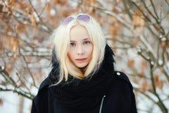 关闭冬天画象:在一件温暖的羊毛夹克打扮的年轻白肤金发的妇女摆在外面在有叶子后面的一个多雪的城市公园 免版税库存图片