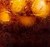关闭冰块的看法在可乐背景中 免版税库存照片