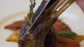 关闭切开用刀子的新鲜的鲜美肋骨由客户客人在luxary餐馆 水多的烤肋骨与 股票视频