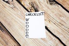 关闭别针和做名单在稠粘的笔记的清单词有木背景 免版税库存图片