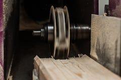 关闭削减一个凹线或凹凸缝在橡木片断的平直的路由器位  库存图片