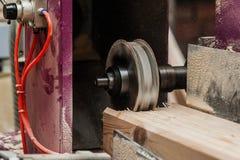 关闭削减一个凹线或凹凸缝在橡木片断的平直的路由器位  库存照片