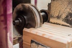 关闭削减一个凹线或凹凸缝在橡木片断的平直的路由器位  免版税库存照片