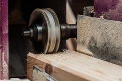 关闭削减一个凹线或凹凸缝在橡木片断的平直的路由器位  免版税库存图片