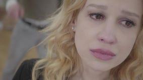 关闭前景哭泣的白肤金发的妇女,叫喊和呼喊在背景的一个情感恼怒的人 夫妇 股票录像