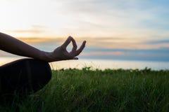 关闭剪影手 妇女做室外的瑜伽 妇女健身生活方式俱乐部的行使重要和凝思在日落b 图库摄影