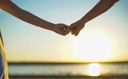 关闭加入手的两个恋人 男人和妇女藏品细节剪影移交Sunset湖背景 夫妇Tru 免版税库存照片
