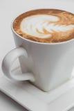 关闭加奶咖啡咖啡杯 在木桌上的拿铁艺术在咖啡馆 免版税库存图片