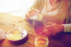 关闭加柠檬的妇女到茶杯 免版税库存照片