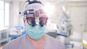 关闭医生佩带的玻璃、一个特定工具和面具的面孔 专业医生画象 股票视频