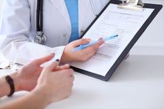 关闭医生和患者手,当phisician指向入病史形式剪贴板时 库存照片