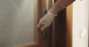 关闭医生在关闭门的橡胶手套的` s手 股票录像