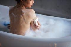 关闭华美的有肥皂的女孩洗涤的胳膊播种的画象  免版税库存照片