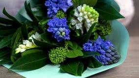 关闭卖花人在照相机前面的桌上把白色和蓝色花花束放 影视素材