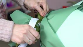 关闭卖花人阻塞花花束与一条绿色和白色丝带的待售 影视素材