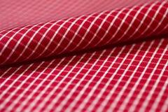 关闭卷条纹与衬衣空白线路的织品红色  免版税库存图片
