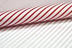 关闭卷稀薄的红线和衬衣白色织品  库存图片