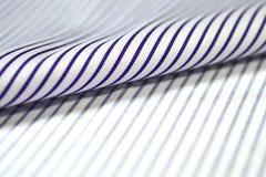 关闭卷稀薄的紫色线和衬衣白色织品  免版税库存照片