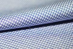 关闭卷蓝色镶边的衬衣的织品和白色  免版税库存图片