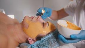 关闭参观美容院,果子面具是应用的在面孔用一根特别木棍子的人 库存图片