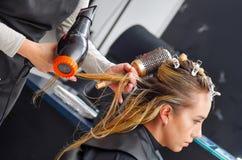 关闭发廊的一名美丽的妇女和烘干有吹风器和圆的刷子的美发师白肤金发的湿头发 库存图片