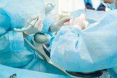 关闭口腔外科过程-安放 有助理的牙医外科医生现代诊所的 口腔医学和医疗保健conce 免版税库存图片