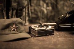 关闭古巴雪茄和烟灰缸在木桌上 共产主义独裁者司令员桌在暗室 军队普通工作 免版税库存照片