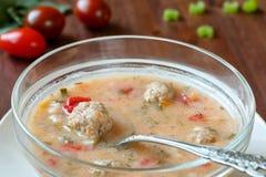 关闭可口自创丸子汤用蕃茄、辣椒粉、芹菜、红萝卜和米在一个玻璃碗在一张木桌上 免版税库存图片