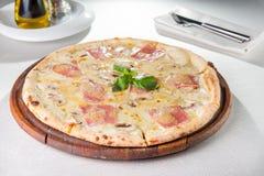 关闭可口薄饼用烟肉,切的蘑菇和乳脂干酪在木板在服务的restauran 库存图片