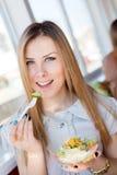 关闭吃可口沙拉美丽的少妇画象获得乐趣在餐馆或咖啡店愉快的微笑 免版税库存照片