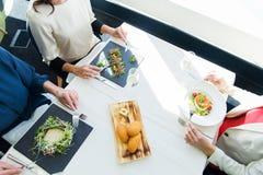 关闭吃开胃菜的妇女在餐馆 图库摄影