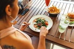 关闭吃沙拉的年轻可爱的妇女在街道咖啡馆 免版税图库摄影