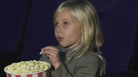 关闭吃玉米花的一个可爱的小女孩,当在电影院时 免版税库存照片