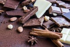 关闭各种各样的巧克力片堆在黑暗的木背景的 黑暗、牛奶、白色和坚果巧克力块 桂香, sta 免版税库存照片