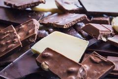 关闭各种各样的巧克力片堆在黑暗的木背景的 黑暗、牛奶、白色和坚果巧克力块 免版税图库摄影