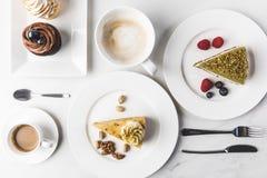 关闭各种各样的蛋糕片断的安排看法在板材、咖啡和杯形蛋糕的 免版税库存照片