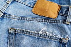 关闭后面口袋和老牛仔布斜纹布棕色皮革标记  免版税库存照片