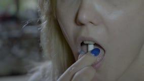 关闭吞下抗生素一次一个和下降第二个的一名白肤金发的妇女从她手 影视素材