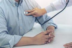 关闭听与stethosco的耐心心跳的医生 库存照片