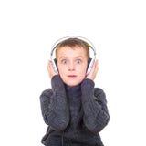 关闭听到与headp的音乐的惊奇的男孩画象  免版税库存照片