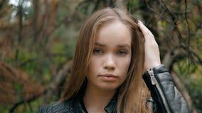 关闭吹在风的美丽的年轻深色的性感的妇女头发画象在森林里 股票视频