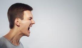 关闭呼喊充满愤怒的人的面孔 啼声和立场在外形 在灰色背景 复制空间 免版税图库摄影