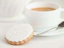 关闭咖啡杯和方旦糖被盖的曲奇饼 在上面的生日快乐装饰 库存照片