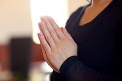 关闭哀伤的妇女祈祷的神在教会里 库存图片