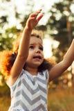 关闭哭泣为注意的不快乐的小孩女孩画象  温暖的阳光 在逗人喜爱的礼服的之字形印刷品 免版税库存图片