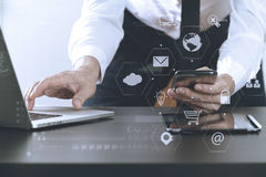 关闭商人与巧妙的电话和膝上型计算机一起使用和 免版税图库摄影