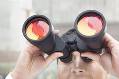 关闭商人看通过双筒望远镜的,在玻璃的红色反射 库存图片